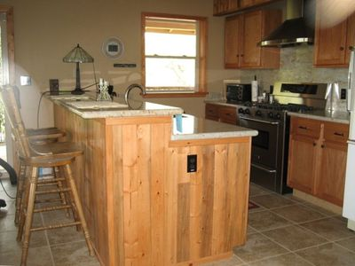 fully equipped kitchen with granite counter tops & gas range