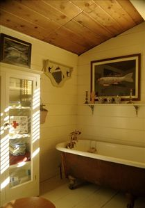 Bathroom has clawfoot tub, handheld shower, and pedestal sink.