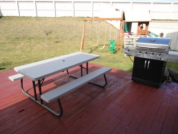 Privately fenced backyard with propane BBQ, play center, and picnic table.