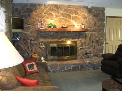Living Room with flat screen TV, wood fireplace and ample seating.