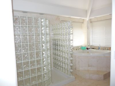 Master bathroom with walk in shower and Jacuzzi bathtub tiled in marble.