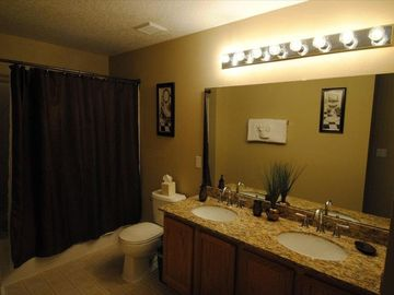 En-suite bath with new granite counters, under mount sinks, faucets and decor