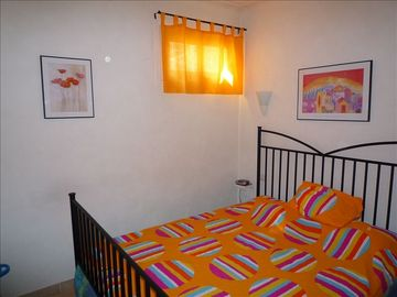 Bedroom is bright and colorful with a queen bed