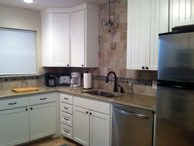 Kitchen has stainless steel appliances, including a dishwasher, and granite