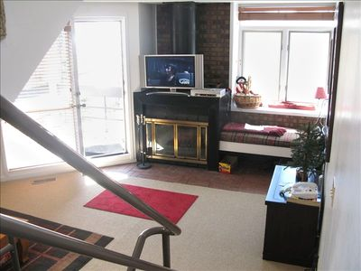 Living room w/ wood fireplace,deck, big screen cable TV/DVD, spacious windowseat