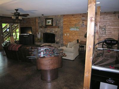 Gameroom with rock fireplace, Nintendo Wii, and wagon wheel game table