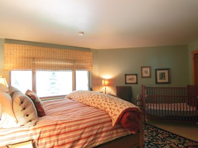 Bedroom on middle level with queen bed, double sink bathroom and crib