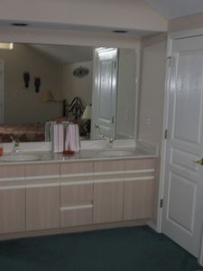 The elegant master bathroom contains ample storage and preparation space
