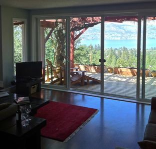 Living room, looking through a wall of glass onto the deck, forest and lake