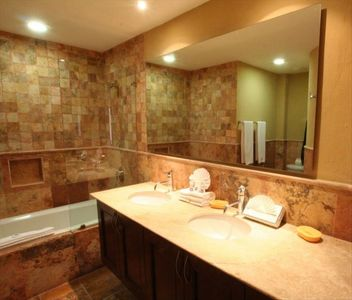 Marble bathroom has shower and bathtub, towels/linens included