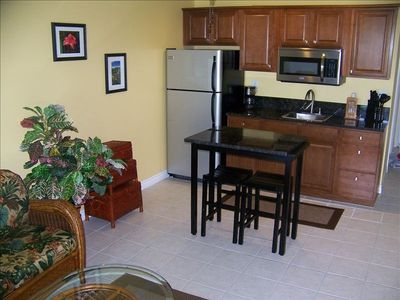 Kitchenette area with Granite Countertop, full size Refrigerator and Microwave.