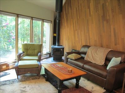 Huge glass wall with the forest outside the door and warm cozy stove