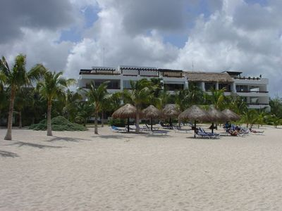 A sandy beach with plenty of lounge chairs. The palapas offer shade.