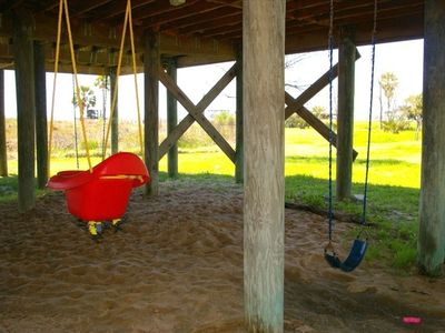 Cool play area under the house for the baby and kids swings and sand.
