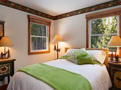 Main floor bedroom, all new luxury bedding and a view to the surrounding pines
