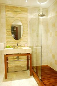 Master bathroom with wood-slatted shower, leather, glass and limestone vanity