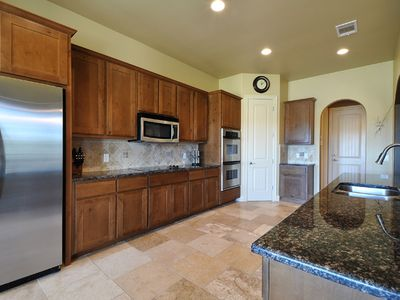Kitchen w/ stainless double ovens, microwave, dishwasher & fridge