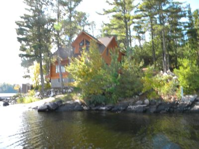 View of log lodge from lake facing west