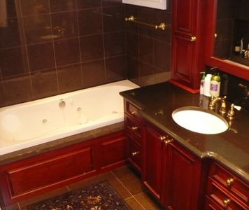 Stockbridge house rental - Master bathroom with cherry wood cabinetry
