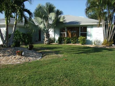 Well maintained home with manicured lawn and tropical flower garden