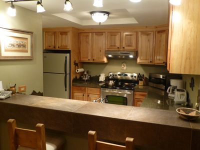Remodeled kitchen with Hickory cabinets stocked with dishes and utensils