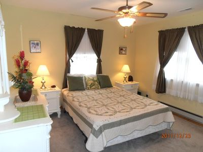 Master bedroom with queen size bed and full length mirrors and closet