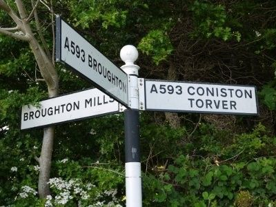 Local sign post shows turning to Broughton Mills