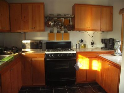 Fully equipped kitchen with 4 burner propane stove, oven, microwave, & frig