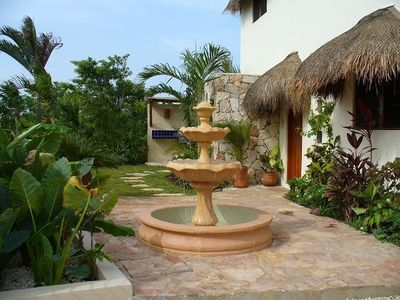 The tropical entry courtyard features a fountain and a gas BBQ