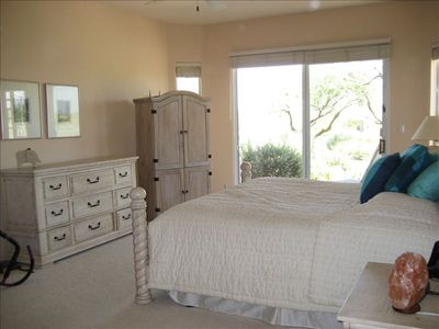 Huge master bedroom that has sliding doors that open to back patio