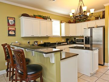 Well-stocked kitchen with granite and stainless steel appliances