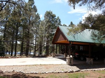 Pagosa Springs lodge rental - Front of house with Lake Forest in background. Paved carport + huge garage.