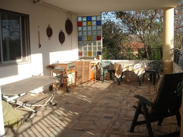 The shaded patio with outdoor furniture and BBQ