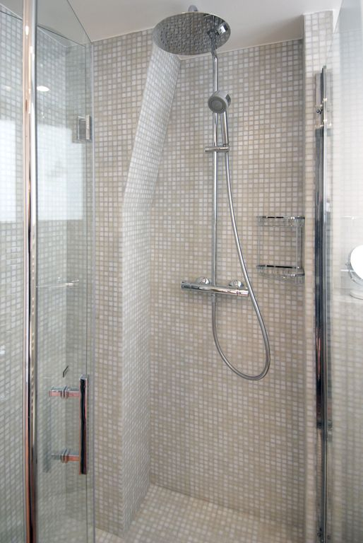 The large shower has glass mosaic tiles