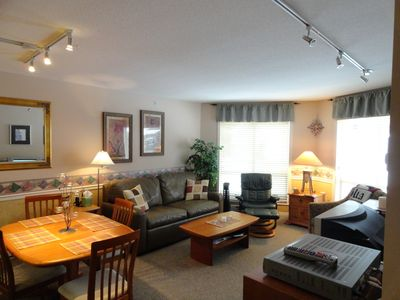spacious living area, leather sofa and recliner cherry wood furniture.