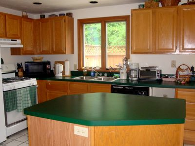 Kitchen with island, new stainless refrigerator, dish washer, gas stove and oven