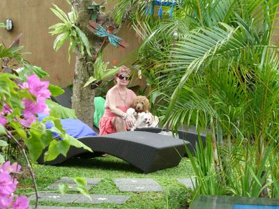 Sandy relaxing under the Mango tree with her dogs after doing finishing touches.