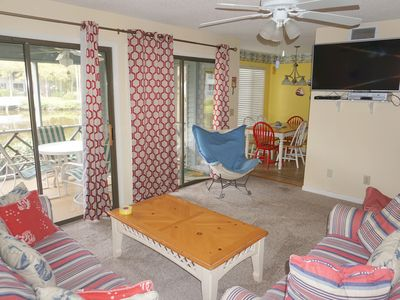 Bright family room with a flat screen TV and a lagoon view off the screen porch.