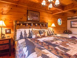 Pigeon Forge cabin photo - mainfloor master suite with comfy king size log bed with large jetted jacuzzi