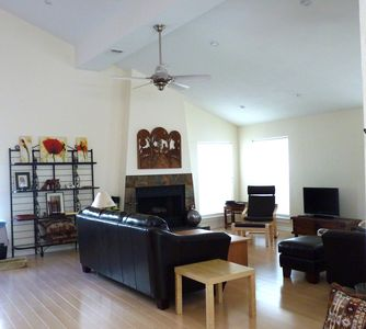 Large, spacious family room with leather furniture and laminated flooring