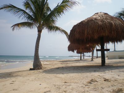 Quiet, white, sandy beach with palapas lies between the pool and ocean.