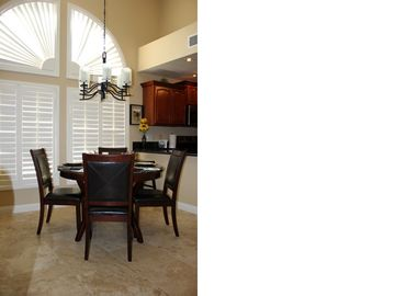 Plantation shutters over cherry and leather dining room