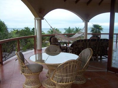 Large covered deck with patio furniture looking out to the sea