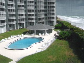Satellite Beach condo photo - View of pool & ocean from screened balcony