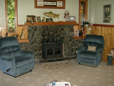 River rocked fireplace w. woodstove glass doors to view coziness of fire.