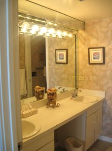Master dressing area has two sinks, hair dryer and brightly lit mirror.