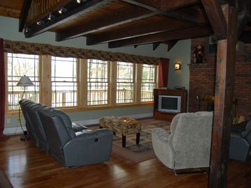 Living room in main home with fireplace and views of lake. Loft above.