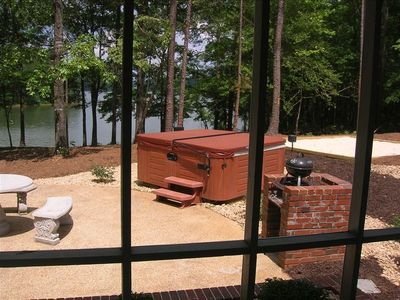 View of hot tub, lake and sand area through screened in porch