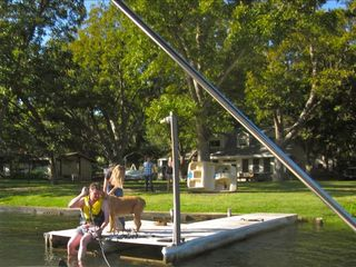 Dock, pecan tree shaded lawn with house in background. Paddleboat against tree.
