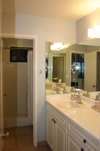 The bathroom features a walk-in shower and an anteroom with vanity and sink.